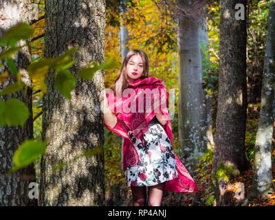 Nature-lover teen girl countrygirl in woodland forest amongst trees wearing red scarf and short skirt mini miniskirt serious indifferent indifference - Stock Image