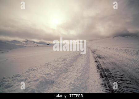 Scenic view of landscape covered with snow against sky - Stock Image