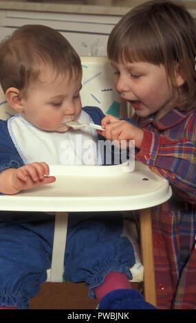 little girl spoonfeeding her baby sister - Stock Image