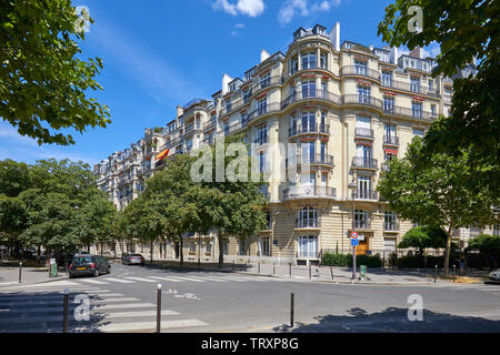 PARIS, FRANCE - JULY 21, 2017: Ancient luxury buildings facade and empty street with trees in a sunny summer day in Paris, France - Stock Image