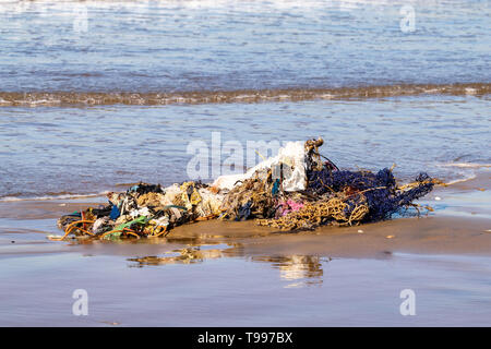 Clothes and rubbish washed up onto sand beach by the Atlantic Ocean, Agadir, Morocco - Stock Image