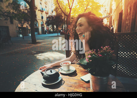 Laughing beautiful white caucasian girl with black curly hair and teal ring sitting in street cafe next to wooden - Stock Image