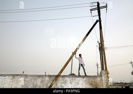 A guy stans on a wall near electric pylons in Arif Nagar Colony. Bhopal, India - Stock Image