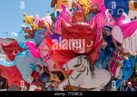 A display of childrens helium filled cartoon foil balloons - Stock Image