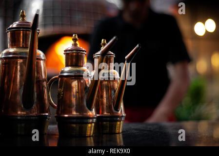 classic olive oil copper cruet traditional dispenser detail in italian restaurant - Stock Image