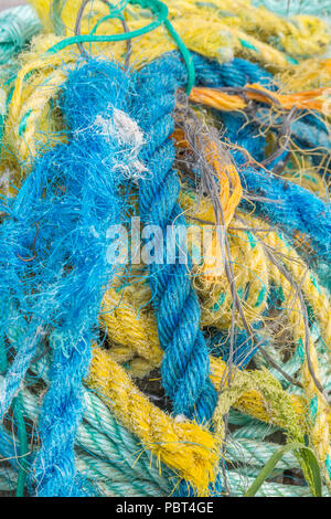 Colourful pile of old and frayed plastic ropes and netting used for fishing. - Stock Image
