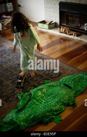 Inflatable crocodile series. Girl aged five blows up crocodile - Stock Image