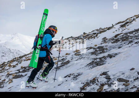 Skier hiking to the summit of La Capa on a powder day. - Stock Image