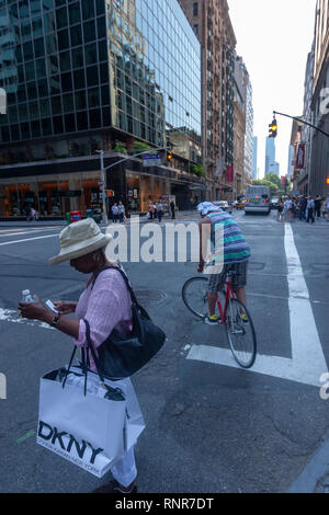 Afro American woman with DKNY bag and a cyclist in E 60th, New York City, USA - Stock Image