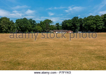 Fleet, Hampshire, UK. 6th July 2018. UK Weather, village cricketers should enjoy ample opportunities to score on hard, fast outfields as the UK drought continues and the outfield turns brown. Credit: Images by Russell/Alamy Live News - Stock Image