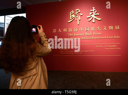 Beijing, China. 24th Apr, 2019. A visitor takes photos at the entrance of the exhibition at the National Museum of China in Beijing, capital of China, April 24, 2019. Chinese cultural relics returned from Italy are on display at the National Museum of China in Beijing from April 24 to June 30. The exhibition, titled 'The Journey Back Home' showcases more than 700 pieces of returned Chinese artifacts. Credit: Li He/Xinhua/Alamy Live News - Stock Image