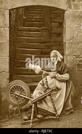 Woman at a spinning wheel near Dinan, Brittany, Northern France. - Stock Image