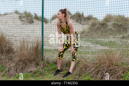 sporty woman resting with her hands on her kness catching her breath - Stock Image