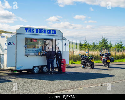 Two Motorcyclists stop for refresment at The Bordere Café van at Carter Bar on the A68 English Scottish Border - Stock Image