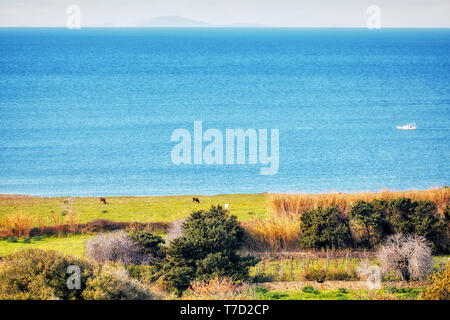 From above view of a meadow field sea sky clouds and a boat in Gumusluk, Bodrum Mugla Turkey - Stock Image