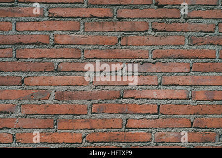 Texture of accurate and old wall composed of oblong red brick thick cement seams - Stock Image