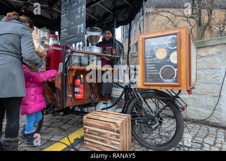 Dresden, Germany, December 15., 2018: Seller for coffee speciality on a Coffee bike, a converted bicycle with a high-quality coffee maker, operated wi - Stock Image
