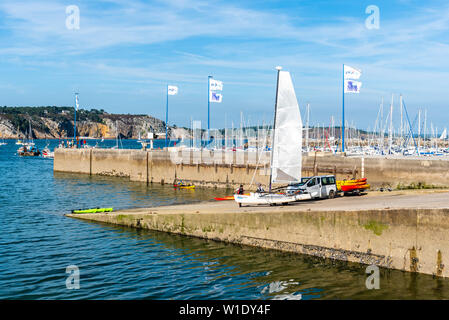 Morgat, France - August 4, 2018:  People taking out the water and storing canoes, kayaks and a catamaran in the marina of Morgat a sunny day of summer - Stock Image