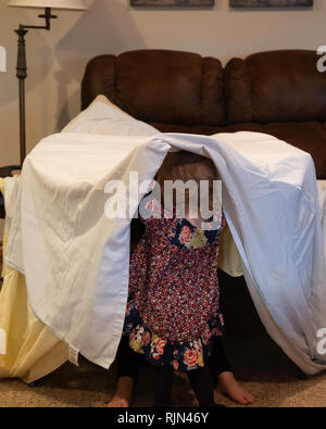 Two Caucasian girl children playing with makeshift tent made from a sheet draped over furniture indoors. - Stock Image