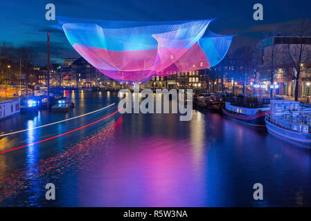 Amsterdam illuminated in winter time during Amsterdam Light Festival with light trails of passing round trip boat. - Stock Image