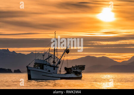 Seiner anchored in Amalga Harbor at sunset awaiting a commercial salmon opening, Southeast Alaska; Juneau, Alaska, United States of America - Stock Image