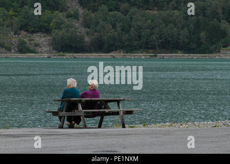 Skjolden, Norway - 6 August 2018: Two elderly tourist sit by a bence on the shores of the Sogenfjorden fjord in village of Skjolden on 7 August 2018. The village is set at the inner end of Sogenfjorden, the world's longest fjord and the deepest in Norway with its sheer vally walls and jagged mountain peaks. Photo: David Mbiyu - Stock Image