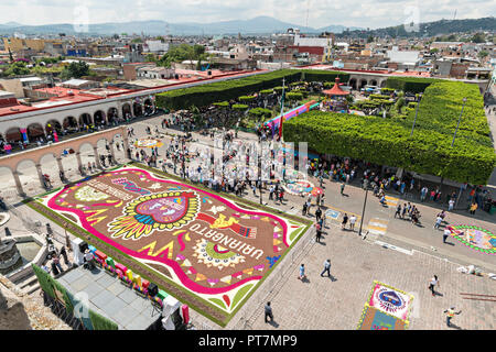 A giant football field size floral carpet decorates the town square in front of the Parroquia San Miguel Archangel church in the central Mexican town of Uriangato, Guanajuato. Every year residents create giant floral carpets made from colored sawdust and decorated with flowers during the 8th Night Celebration marking the end of the Feast of St Michael. Uriangato became an international sensation after wowing Brussels with their floral carpet displayed at the Brussels Grand-Place during the Belgium Floral Carpet festival. - Stock Image