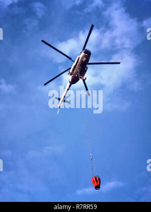 Fire Fighting Helicopter, ER-MHZ Mil Mi-8MTV-1 heavy lift helicopter with a water carrying Bambi Bucket hanging from a 30 metre long line. - Stock Image
