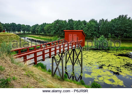 Outhouses at Vesting Bourtange, the star-shaped fortress in Groningen Province, The Netherlands, were built over the moat. - Stock Image