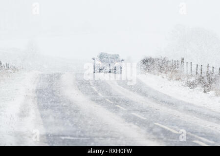 Stirlingshire, UK. 10th March 2019. : UK weather - a car is barely visible during a very heavy snow shower on the A875 road near Balfron, Stirlingshire Credit: Kay Roxby/Alamy Live News - Stock Image