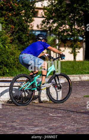 Cyclist on a mountain bike preparing to do bike tricks in the city. - Stock Image