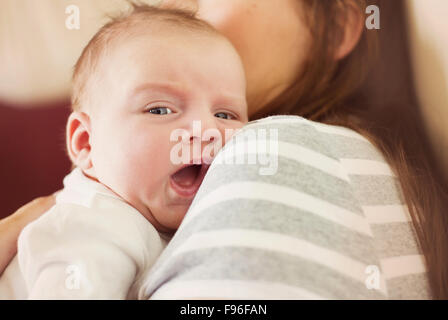 Cute newborn baby boy relaxing at home with his mother - Stock Image