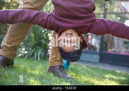 Playful boy hanging upside down - Stock Image