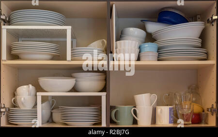 Domestic kitchen cupboards interior with stacked crockery - Stock Image