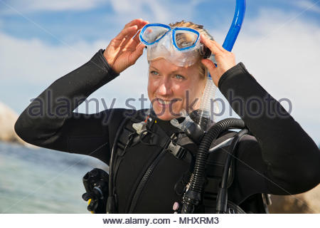 Female scuba diver adjusting mask before ocean diving from beach - Stock Image