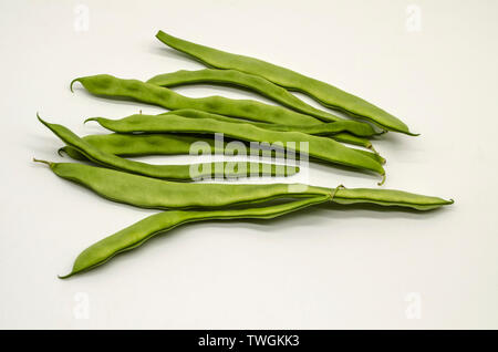 Prepared for use in cooking, immature tender green bean pods on white background - Stock Image