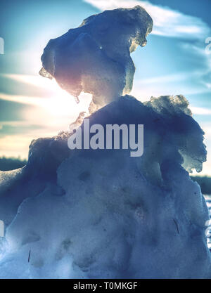 Melting icy snow manin landscape. People walk in winter sunny day around. Holes in snowman body - Stock Image