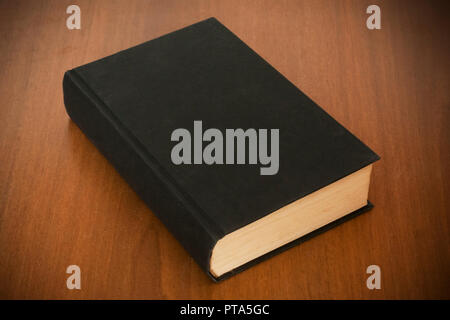 Blank old black book on wooden table ready for mockup or cover customization - Stock Image