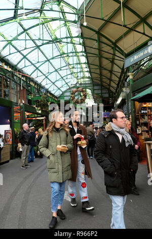 People visiting Borough Market at Christmas looking at produce inside on stalls in Southwark South London England UK  KATHY DEWITT - Stock Image