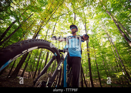 Low angle view of male cyclist on bicycle in forest - Stock Image