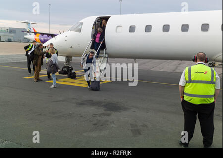 People disembarking from unmarked aircraft at Bristol Airport - Stock Image