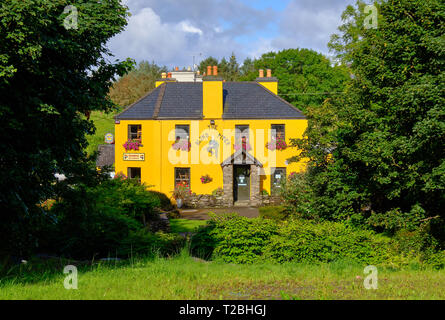 The Blind Piper, a yellow typical Irish pub in County Kerry on a sunny day, framed by green trees. Caherdaniel, Ireland, - Stock Image