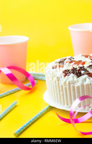 Sponge layer birthday cake with whipped cream frosting milk chocolate star sprinkles strawberry jam. Pink paper drinking cups blue straws curly ribbon - Stock Image