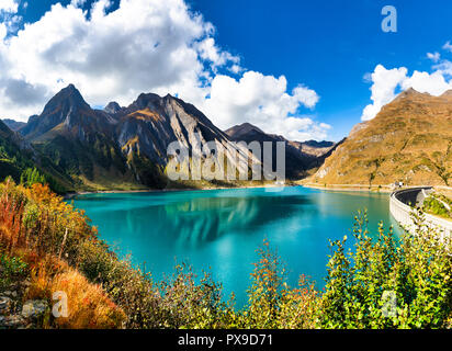 scenic landscape in autumn season from lake of Morasco in high Formazza valley with turquoise water and mountains in background - Stock Image