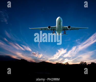 An artistic skyscape view of a commercial jet aircraft flyng in a vibrant blue sky, with bright white coloured Cirrus clouds. Atmospheric beauty in na - Stock Image