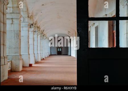 Pillar lined corridor with selective focus on doorway. - Stock Image