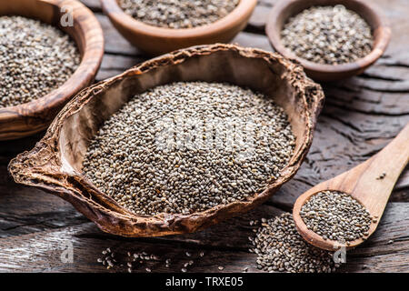 Chia seeds in different dishes on old wooden table. Top view. - Stock Image
