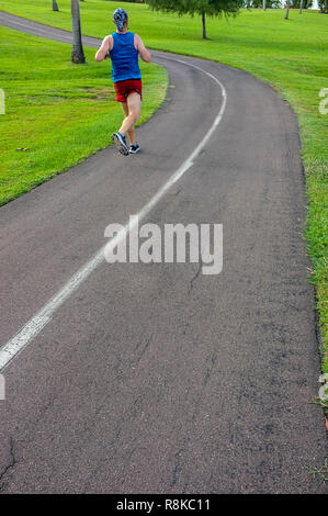 Man jogging on the cycling and walking track in Fannie Bay, Darwin, Northern Territory, Australia. - Stock Image
