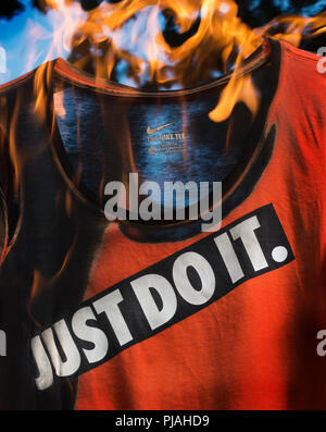 """09/05/2018, Studio, Lexington, MA, USA.  Flaming NIKE sports shirt, Editorial illustration.  On 09/03/2018 NIKE Inc. a global Sportswear company announced that they will feature Colin Kaepernick in the 30th anniversary of NIKE's slogan """"Just Do It"""" ad campaign. - Stock Image"""