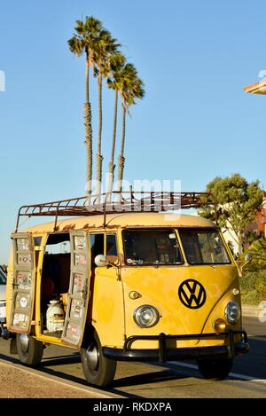 Classic 1960s yellow Volkswagon VW minibus camper van parked at Sunset Cliffs at sunset, doors open with palm trees, San Diego, USA - Stock Image